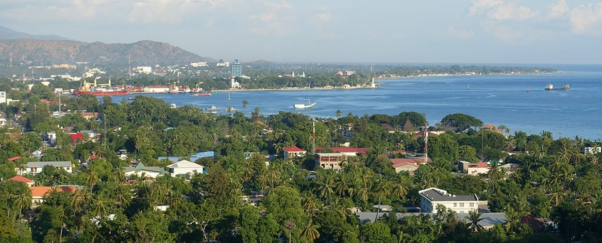 Timor-Leste: Aerial View, Landscape, Nature, Outdoors, Scenery, Building, House, Housing, Villa, Conifer, Flora, Plant, Tree, Mansion, Countryside, Pine, Yew, City, Town, Urban, Abies, Fir, Downtown, Campus, Office Building, Promontory, Coast, Ocean, Sea, Water, Neighborhood, Forest, Land, Rainforest, Vegetation, Architecture, Convention Center, Hotel, Resort, Bush, Arecaceae, Palm Tree, Apartment Building, High Rise, Jungle, Harbor, Port, Waterfront, Spruce, Beach, Monastery
