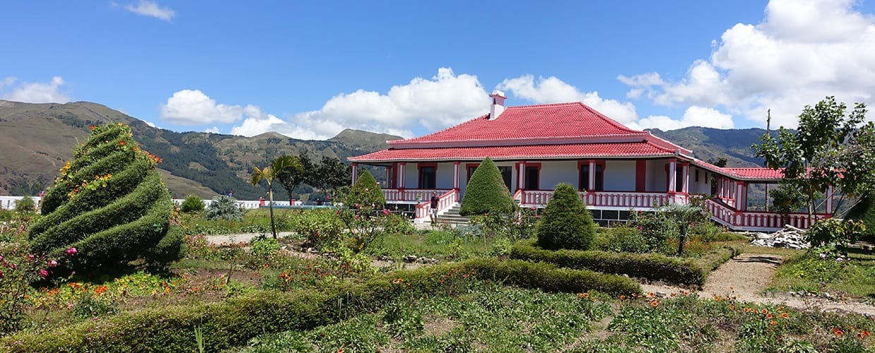 Timor-Leste: Building, Cottage, House, Housing, Villa, Bush, Flora, Plant, Vegetation, Conifer, Tree, Yew, Countryside, Nature, Outdoors, Backyard, Yard, Spruce, City, Town, Urban, Apartment Building, High Rise