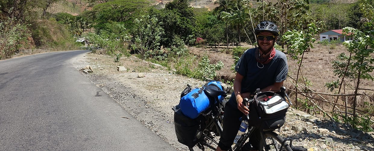 Timor-Leste: Human, People, Person, Motorcycle, Transportation, Vehicle, Bicycle, Bike, Path, Trail, Countryside, Farm, Nature, Outdoors, Rural, Flora, Plant, Vine, Forest, Land, Tree, Vegetation, Soil, Cyclist, Sport, Sports, Conifer, Yew, Wilderness, Rainforest, Jungle, Oak, Sycamore, Dirt Road, Gravel, Road
