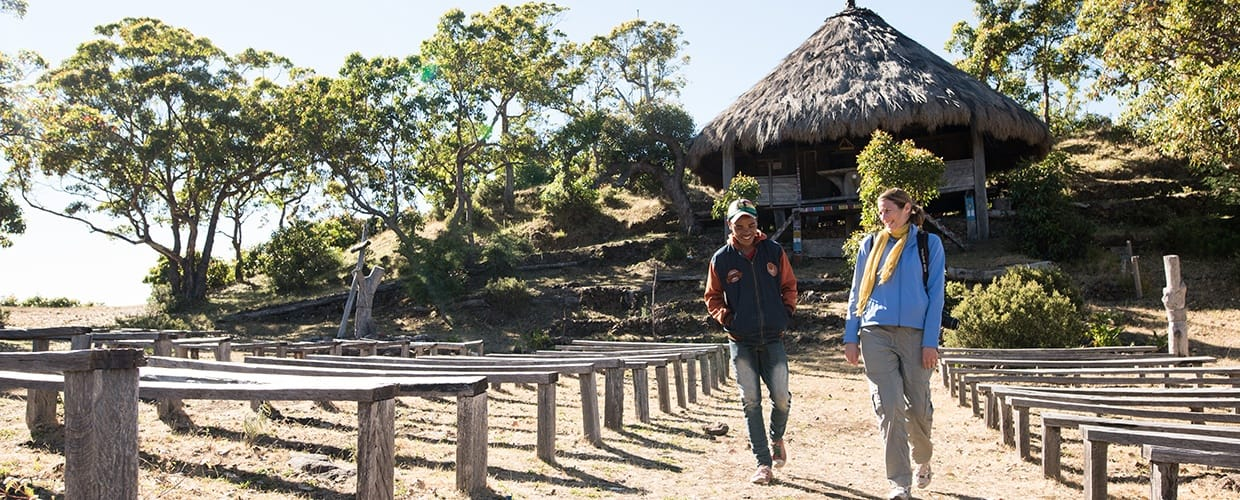 Timor-Leste: Human, People, Person, Bench, Clothing, Coat, Overcoat, Suit, Leisure Activities, Building, Cottage, House, Housing, Villa, Outdoors, Countryside, Nature, Tourist, Path, Trail, Flora, Plant, Hotel, Resort, Forest, Land, Tree, Vegetation