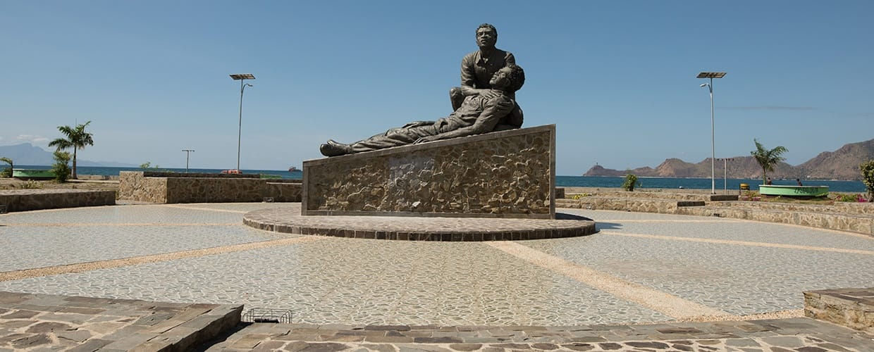 Timor-Leste: Human, People, Person, Monument, Art, Sculpture, Statue, Dirt Road, Gravel, Road, Fountain, Water, Architecture, Building, City, Downtown, Plaza, Town, Town Square, Urban, Outdoors, Sand, Soil