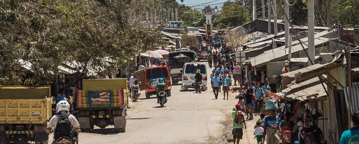 Timor-Leste: Human, People, Person, Market, Path, Walkway, Alley, Alleyway, Building, City, Road, Street, Town, Urban, Crowd, Pavement, Sidewalk, Moped, Motor Scooter, Motorcycle, Transportation, Vehicle, Vespa, Bench, Freight Car, Shipping Container, Flora, Forest, Land, Nature, Outdoors, Plant, Tree, Vegetation, Bazaar, Shop, Neighborhood, Parade