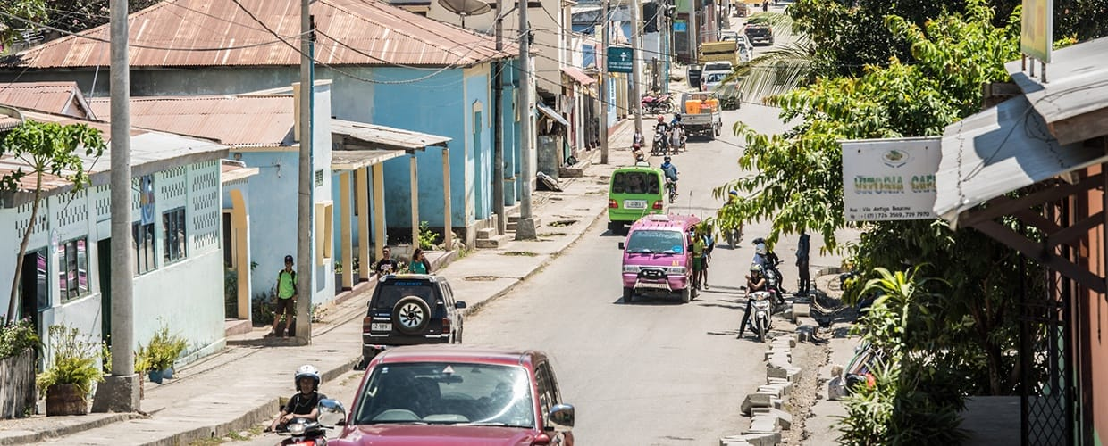 Timor-Leste: Automobile, Car, Transportation, Vehicle, Flora, Jar, Plant, Potted Plant, Pottery, Vase, Path, Pavement, Sidewalk, Walkway, Building, City, Town, Urban, Alley, Alleyway, Road, Street, Neighborhood, Moped, Motor Scooter, Motorcycle, Vespa, Downtown, Architecture, Apartment Building, High Rise, House, Housing, Mansion, Plaza, Town Square, Intersection